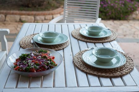 Table for three with salad plate in garden Archivio Fotografico