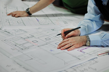 Architects Discussing Plan Together At Desk