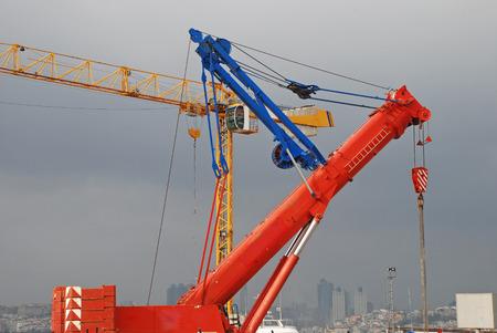 jib: Red crane boom against grey sky Stock Photo