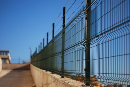 Green wire fence against the blue sky Фото со стока