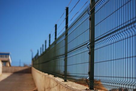 Groene draad hek tegen de blauwe hemel