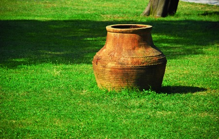 Ancient amphora on green grass photo