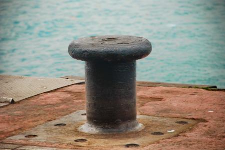 bollard: Rusty old bollard on the dock