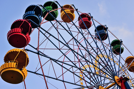 Ferris wheel on the background of blue sky, colorful booths