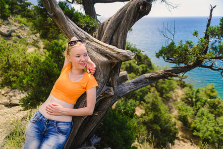 Girl in orange crop top and jeans lying on tree and looking seaward Stock Photo