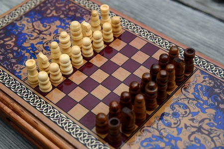 battle plan: Vintage wooden chess on a wooden chess board. Black and white pieces on the board. Stock Photo
