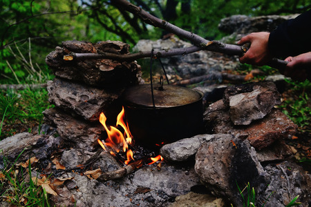 Man holds a kettle over a fire, cooking a meal in a terpohod, hands in a frame Stock Photo