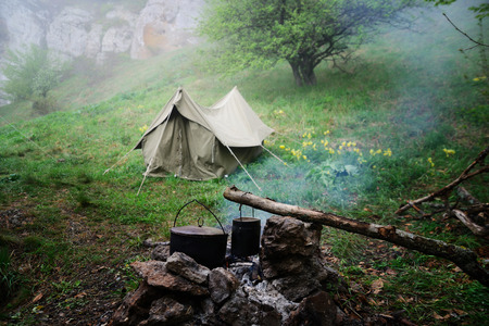Two bowlers at the stake, cooking in the tourist camp, a tent on the background Stock Photo