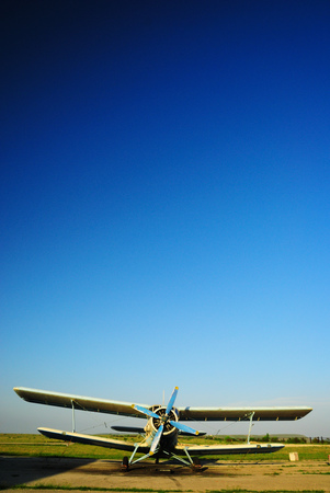 Old light aircraft biplane on the airfield against a clear blue sky Stock Photo