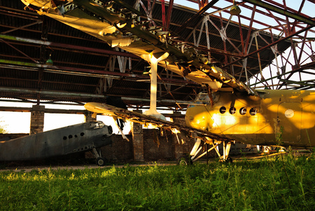 Old retro broken airplane in an abandoned destroyed hangar in the setting sun