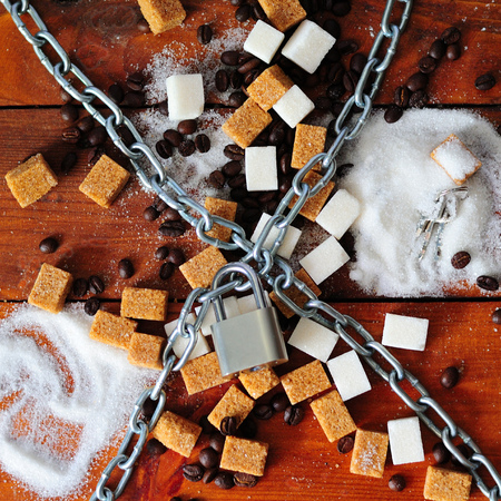 White and brown reed lump sugar and coffee beans under the chain with a lock lie on a wooden background, the concept of a ban on sweet