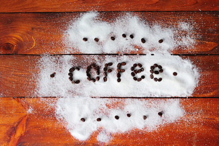Coffee inscription from coffee roasted grains on white scattered sugar on a woody background