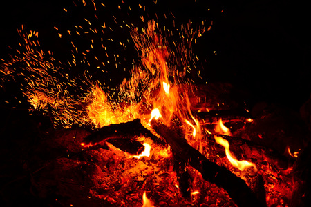 Large burning bonfire with soft glowing flame and sparkles flying all around Foto de archivo