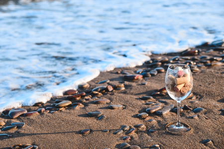 Large wine glass filled with cork stoppers stands on a sandy beach against the sea Standard-Bild