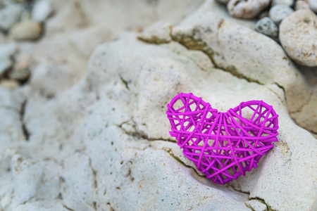 Purple knitted heart on a rocky beach coast, romantic background, space for text