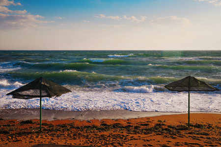 Seascape, sandy beach with two umbrellas in the background of the sea during a storm at sunset Stok Fotoğraf