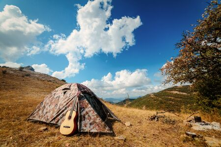 Acoustic guitar near a tent in nature during a camping trip