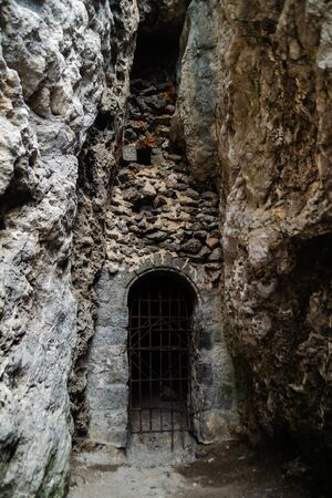 Entrance to the through grotto closed with bars in the rock, Novyi Svet village, Crimea, Russia