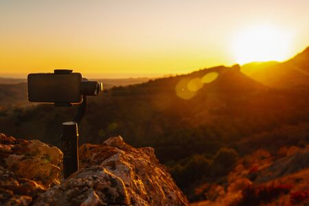 Shooting videos and photos on a mobile phone with 3D stabilizers in the mountains at sunset Stockfoto - 134026058
