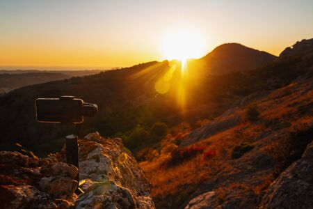 Shooting videos and photos on a mobile phone with 3D stabilizers in the mountains at sunset Stockfoto - 134026060