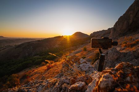 Shooting videos and photos on a mobile phone with 3D stabilizers in the mountains at sunset Stockfoto - 134026061