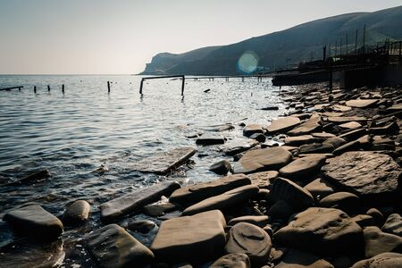 Sea coast with large stone slabs in the evening Stockfoto - 134027849