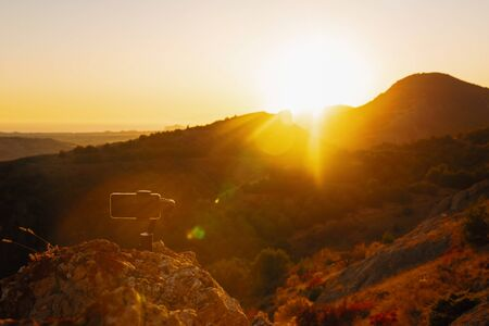 Shooting videos and photos on a mobile phone with 3D stabilizers in the mountains at sunset Stockfoto - 134028068