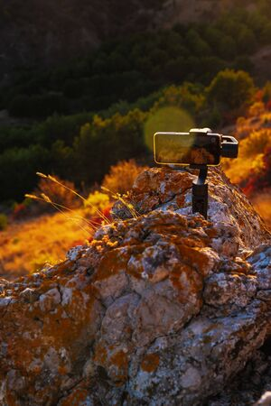 Shooting videos and photos on a mobile phone with 3D stabilizers in the mountains at sunset Stockfoto - 134028078