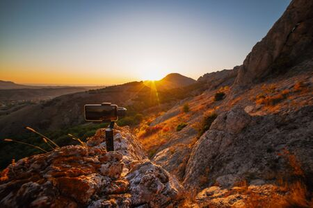 Shooting videos and photos on a mobile phone with 3D stabilizers in the mountains at sunset Stockfoto - 134847112