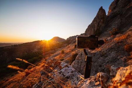 Shooting videos and photos on a mobile phone with 3D stabilizers in the mountains at sunset Stockfoto - 134847113