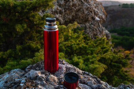 Red  with hot tea on a camping trip in the mountains Stockfoto