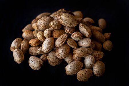 Unpeeled almonds on a black background Standard-Bild - 134847118