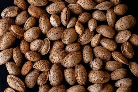 Unpeeled almonds on a black background Standard-Bild - 134847117