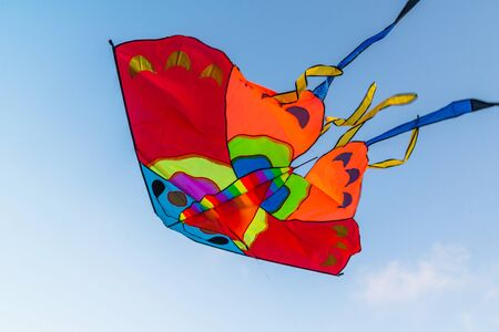 Bright colorful kite flying in the blue clear sky Stockfoto - 134847121