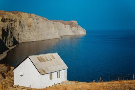 Lonely white house on the edge of a cliff on the sea coast, the concept of silence, solitude, contemplation, meditation