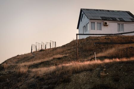 Lonely white house on the edge of a cliff on the sea coast, the concept of silence, solitude, contemplation, meditation Stockfoto - 134847133