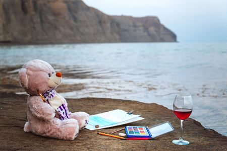 Toy bear with paints and a glass of wine by the sea, hobbies, silence, funicular, loneliness Stockfoto - 134847150
