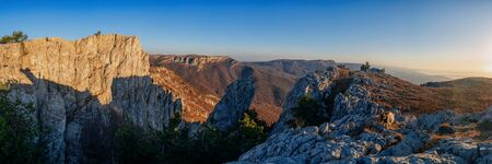 Gorgeous wide panorama of a rocky mountain range in autumn at sunrise