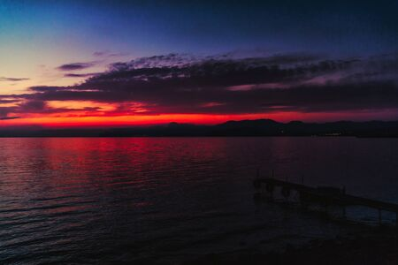 Blue-red sunset over the sea, a small pier for boats on the seashore