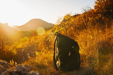 Backpack in the mountains at sunset while walking Stockfoto - 134847209