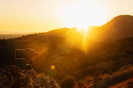 Shooting videos and photos on a mobile phone with 3D stabilizers in the mountains at sunset Stockfoto - 134847210