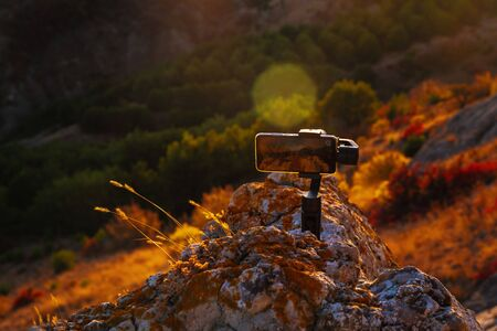 Shooting videos and photos on a mobile phone with 3D stabilizers in the mountains at sunset Stockfoto - 134847211