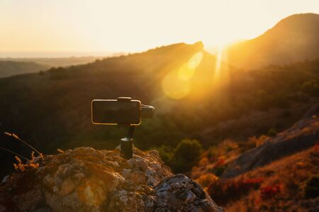 Shooting videos and photos on a mobile phone with 3D stabilizers in the mountains at sunset Stockfoto - 134847212