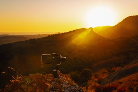 Shooting videos and photos on a mobile phone with 3D stabilizers in the mountains at sunset Stockfoto - 134847213