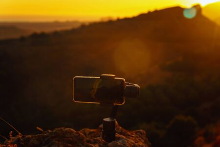 Shooting videos and photos on a mobile phone with 3D stabilizers in the mountains at sunset Stockfoto - 134847214