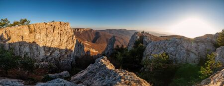 Panoramic view from the top of the rocky mountains and autumn forest in the valley