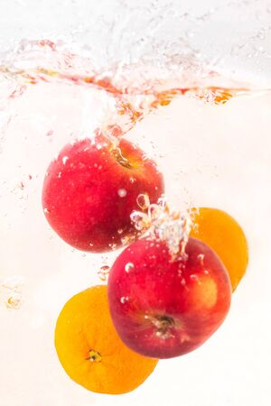 Two red apples and two tangerines with a splash fall into the water in an aquarium on a white background Stockfoto