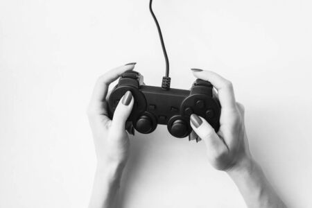 Joystick in female hands on a white background, black and white image
