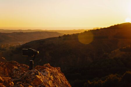 Shooting videos and photos on a mobile phone with 3D stabilizers in the mountains at sunset