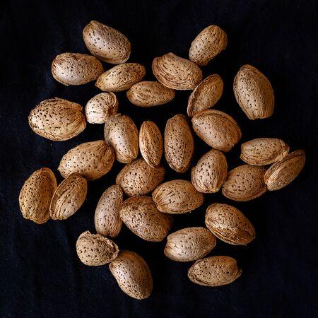 Unpeeled almonds on a black background  Stockfoto